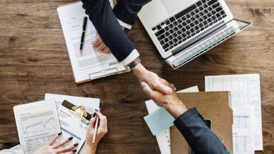 Deux personnes se serant la main au-dessus de contrats signés